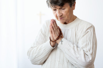Religious elderly woman with rosary in folded hands praying to god