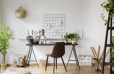 Brown chair at desk with lamp in white workspace interior with plants and pouf. Real photo