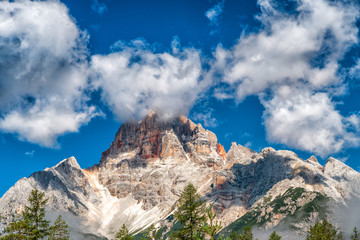 Red colors of Dolomites, Italy. Croda Rossa mountain with blue sky and clouds