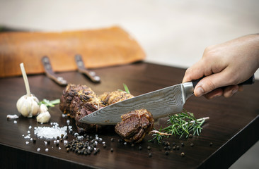 slicing organic roast beef roll on wood table with ingredients