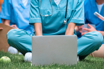 cropped image of medical student studying with laptop on green grass