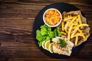 Fish dish - fried fish fillet with french fries and vegetables