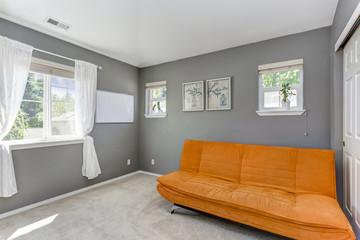 Grey room interior with bright orange sofa.