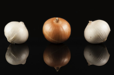 white and gold onions on a black glossy surface