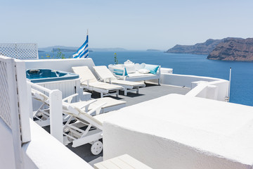 Cozy sunbeds with tiny swimming pool on top of the Oia village at Santorini, Greece.