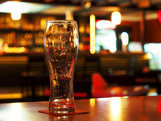 Evening. Empty beer glass on the table in a dark bar. Foam stains inside the glass