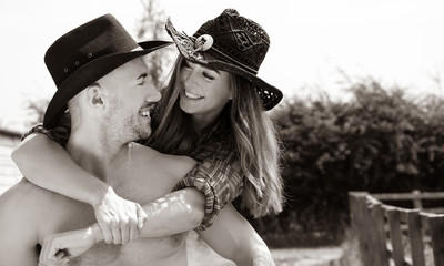 cowboy and cowgirl couple smiling and laughing as he gives her a piggy back ride