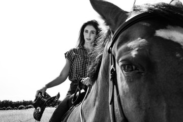 Cowgirl looking at camera while riding horse with western saddle and hat