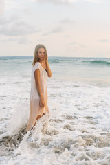 Sexy hipster girl after hot summer day walk in waves in her long trendy summer dress to relax. Fit lady in sand sea beach sunset or ocean sunrise. Travel, active, yoga, freedom lifestyle concept.