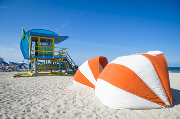 Scenic  view of an iconic yellow and blue lifeguard tower and sunshades on South Beach, Miami
