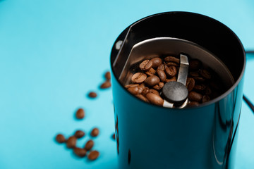 Electric coffee grinder with roasted coffee beans on the kitchen table with blue tabletop. Close-up