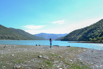Woman taking picture of calm blue lake and mountains, Georgia