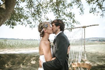 Hochzeitspaar küsst sich bei Outdoor Boho Hochzeit