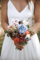 Braut hält Blumenstrauß Outdoor Boho Hochzeit