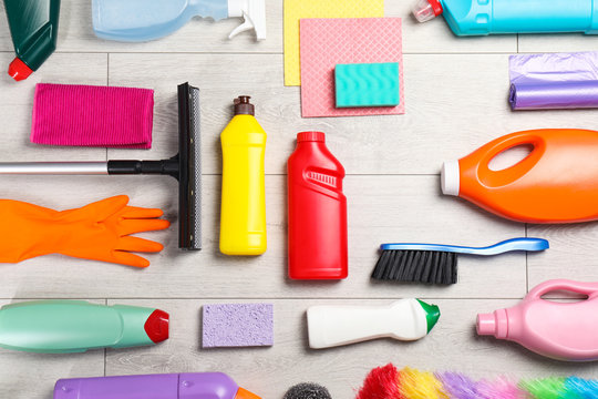 Flat lay composition with cleaning supplies on wooden background