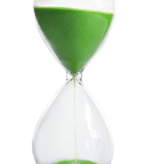 Hourglass with flowing sand on table against white background. Time management