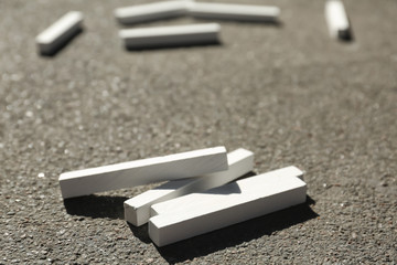 Many white chalk sticks on asphalt, closeup
