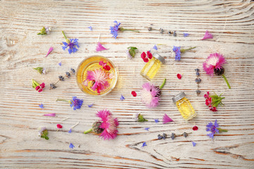 Flat lay composition with essential oils and flowers on wooden background