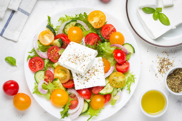 Greek salad with colorful cherry tomatoes red and yellow, cucumber, onion, lettuce and large piece of feta cheese with herbs. In white plate on light background