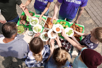 Volunteers serving food for poor people outdoors, above view