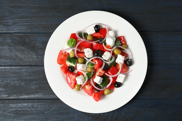 Plate with delicious salad on table, top view