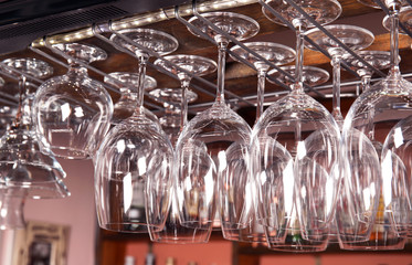 Clean glasses hanging over counter in bar