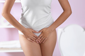 Young woman holding hands on belly at home. Gynecology