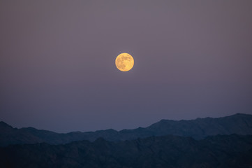 Moon above mountains around in Taba resort town, near the northern tip of the Gulf of Aqaba