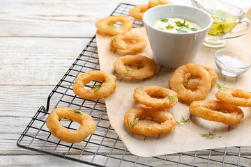 Cooling rack with fried onion rings and sauce on wooden background