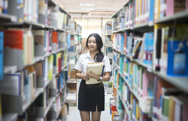 Female students looking for books in the library.