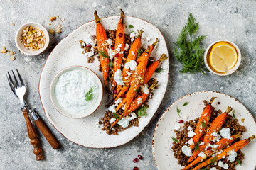 Roasted carrots lentil salad with feta, herb yogurt and dukkah on a light concrete background. Vegetarian food. Top view, flat lay