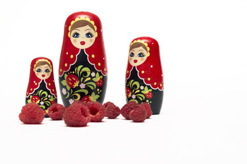 Traditional wooden doll's Matreshka Babushka with raspberries isolated on a white background