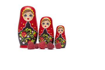 Traditional wooden doll's Matreshka Babushka with raspberries isolated on a white background