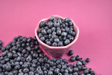 Blueberries in a bowl stock images. Blueberries on a purple background. Healthy summer fruit