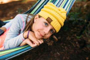 Girl Resting Head on Hands in Hammock