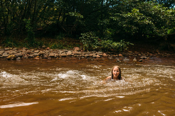Young Girl Swimming in Riverbed
