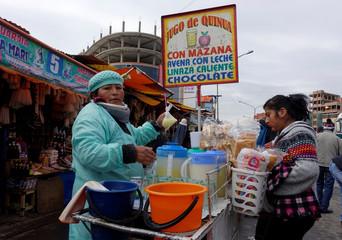 A street vendor offers Quinoa drinks and cheese empanadas in El Alto outskirts in La Paz