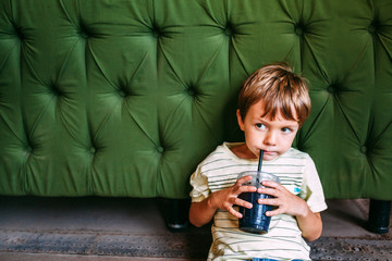 Young Boy Drinking in front of Couch