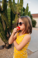 Profile of Girl Eating in Front of Cactus