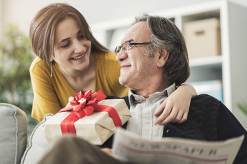 Young woman giving gift her father