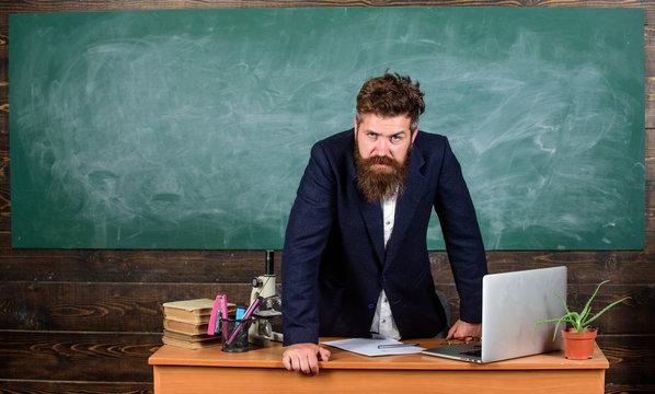 Teacher strict serious bearded man lean on table chalkboard background. Teacher looks threatening. Rules of school behaviour. Man unhappy with behaviour. School principal threatening with punishment