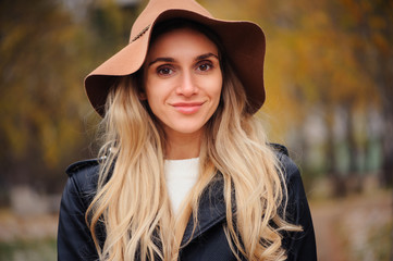 fashion autumn portrait of young happy woman walking outdoor in fall park in hat and leather jacket