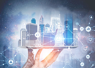 Hand of a man holding a modern city hologram against a nigth city background. Network sketch. Concept of business and HR. Toned image double exposure. Elements of this image furnished by NASA