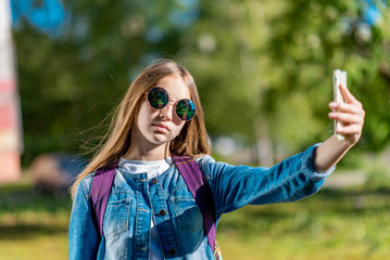 Girl schoolgirl teenager behind backpack. In her hands holds a smartphone in sunglasses. He takes pictures of himself on phone. Rest after school in the city.