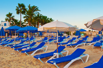 Many white and blue umbrellas and loungers