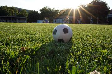 fußball auf rasen im sonnenuntergang