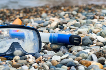 Snorkel and mask on the pebble beach.