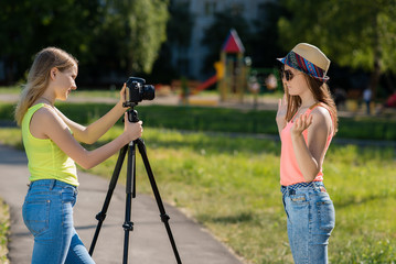Two girls teenager girlfriend. Summer in nature. Writes the video to the camera. In sunglasses and a hat. Use camera with tripod.