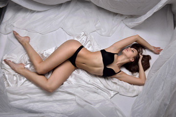Beautiful woman in black underwear laying on the bed.
