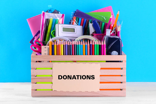 Box with various school and office supplies with a sign on a bright blue background. Donation concept
